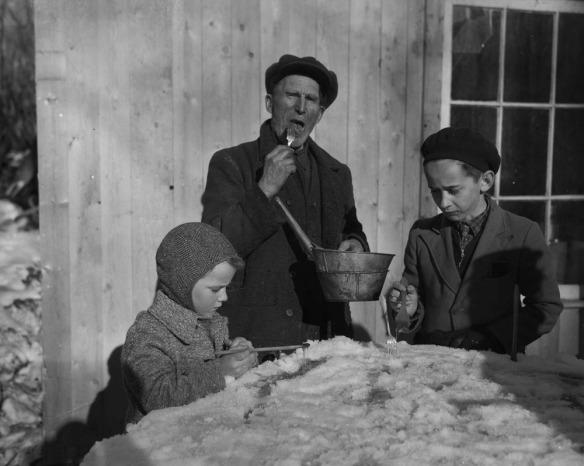 Photographie en noir et blanc montrant trois personnes à l'exteriur mangeant de la tire d'érables