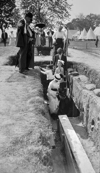 Photo noir et blanc montrant des hommes, des femmes et des enfants dans de beaux habits qui explorent et observent une tranchée canadienne reconstituée dans le cadre d'une exposition en plein air.