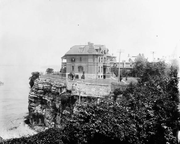 Photographie en noir et blanc d'une grande maison de brique perchée au sommet d'une falaise.