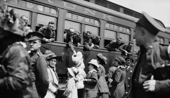 Photo noir et blanc montrant des femmes, des soldats et des enfants rassemblés à l'extérieur d'un train. Des soldats installés aux fenêtres du train semblent saluer leurs familles.