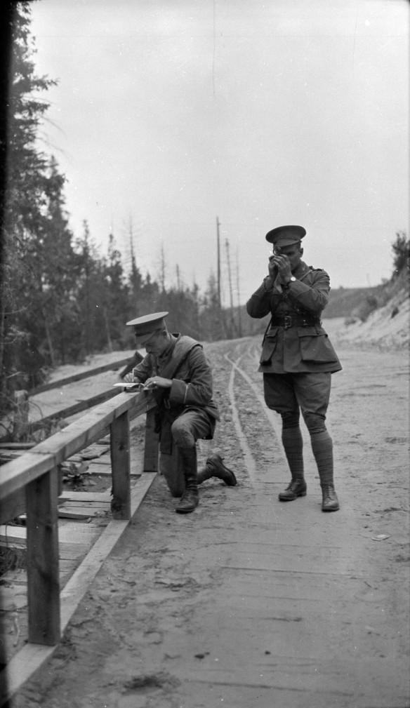 Photo noir et blanc de deux soldats arrêtés sur un chemin de terre. L'un deux lit une boussole pendant que l'autre prend des notes.