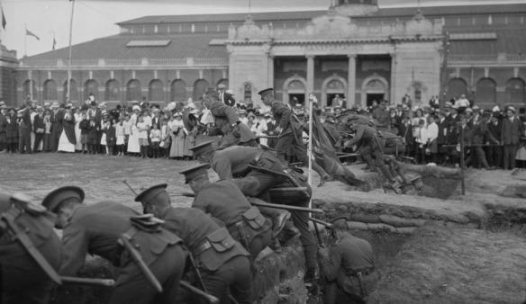 Photo noir et blanc de soldats faisant une démonstration de sortie d'une tranchée devant la foule présente à une exposition.