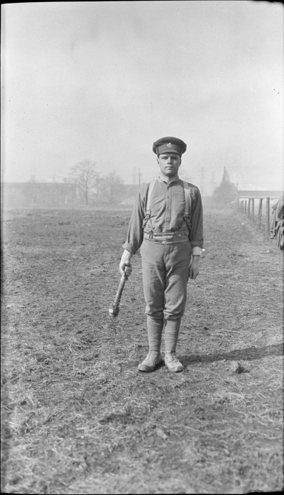Photo noir et blanc d'un soldat debout dans un champ tenant un grand outil (une clé) dans la main droite.