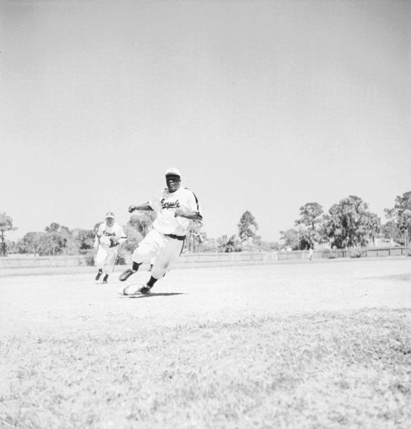Photographie en noir et blanc d'un joueur de baseball qui court sur les coussins. Un pied sur le troisième coussin, il se tourne et se dirige vers le marbre. En arrière-plan, d'autres joueurs et, au loin, la clôture du champ et des arbres.