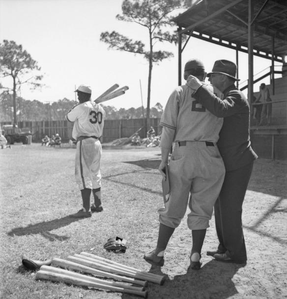 Photographie en noir et blanc de trois hommes sur un terrain de baseball. Deux hommes, dont l'un est vêtu d'un uniforme et l'autre porte une tenue de ville, sont debout en avant-plan et se parlent. Sur le sol, à leurs pieds, on peut voir deux gants de baseball et des bâtons de baseball. En arrière-plan, un autre joueur, en uniforme, tient trois bâtons de baseball reposant sur son épaule droite. Au loin, des gens sont debout ou assis sur le sol ou sur les bancs-gradins.