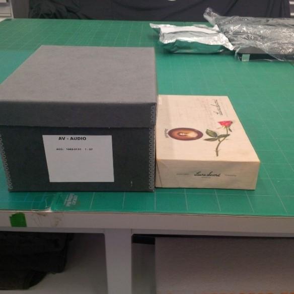 Photo couleur montrant la boîte de chocolat Laura Secord dans laquelle les dictabelts ont été reçus (à droite), et le nouveau contenant dans lequel la collection sera conservée à long terme (à gauche).