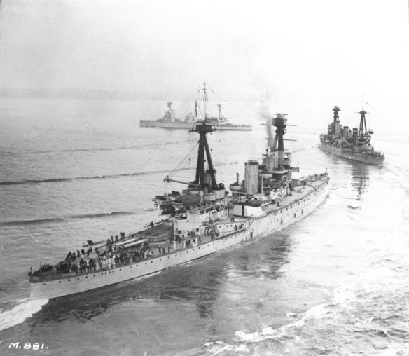 Photographie en noir et blanc de trois grands navires de guerre.