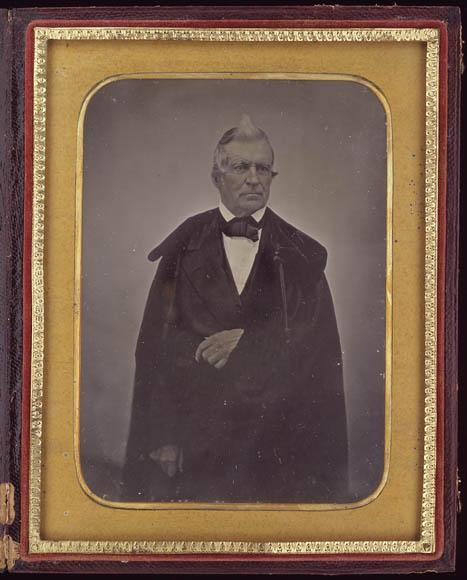 Photographie en couleur montrant l'image d'un homme debout. Le verre est trouble, est aux premiers stades de détérioration. L'image semble voilée.