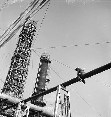 Photographie noir et blanc montrant à partir du sol, en avant plan, un soudeur chevauchant dans les airs un tuyau et en arrière-plan, deux cheminées d'extraction dont l'une est encore entourée d'échafaudage.