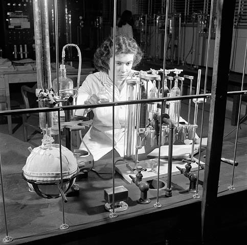 Photographie noir et blanc montrant une technicienne vêtue d'un sarrau blanc, faisant des expériences en face d'un appareil de laboratoire. En arrière-plan, nous voyons de dos une autre technicienne ainsi que d'autres appareils.