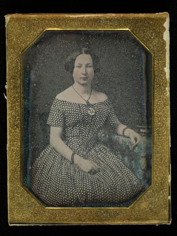 Photographie en couleur dans un cadre doré montrant une femme assise avec le bras accoudé sur une petite table de chevet. Le verre est à un stade avancé de détérioration. On voit le phénomène de transpiration du verre; l'image est floue.