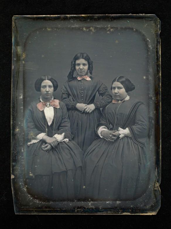 Daguerréotype coloré à la main. Image de trois jeunes femmes; celle du milieu est debout entre les deux autres, assises.