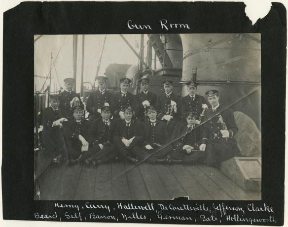Photographie en noir et blanc d'un groupe d'hommes assis ou debout sur le pont d'un navire. La photo est fixée sur un fond noir et arbore, dans le haut, les mots « Gun Room » et une liste de noms, dans le bas.