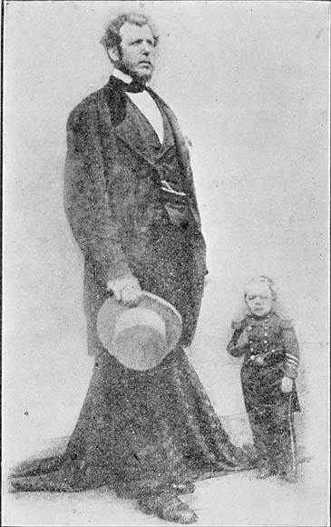 Photographie en noir et blanc de deux hommes debout : l'un est très grand et l'autre est très petit.