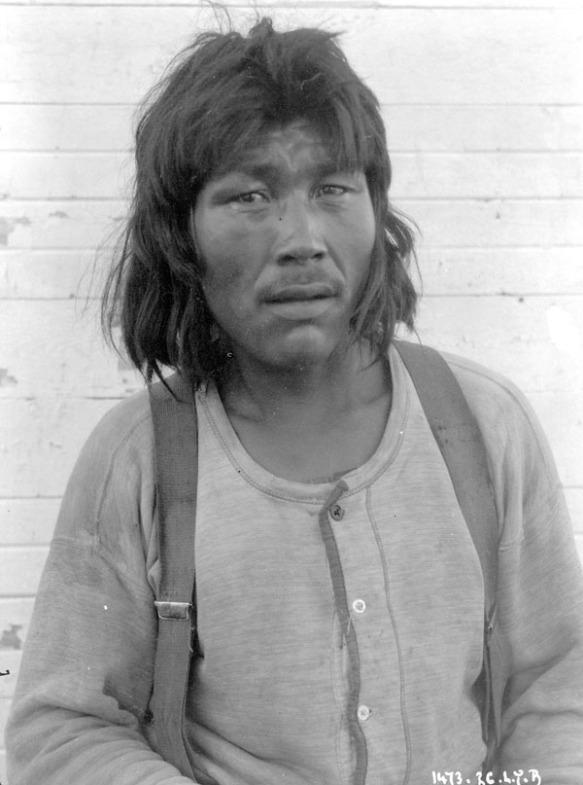 Photographie en noir et blanc d'un homme inuit vêtu d'une chemise et de bretelles et regardant directement le photographe.