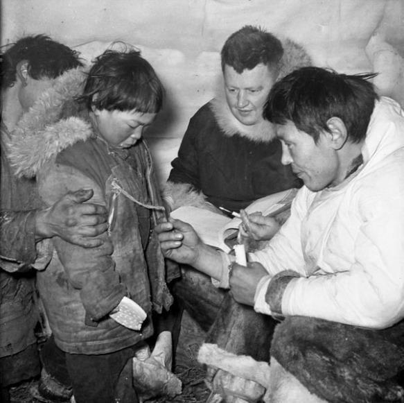 Une photographie en noir et blanc, prise dans un iglou, de deux hommes lisant un numéro de disque attaché au parka d'un jeune garçon.