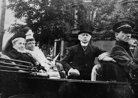 Photographie en noir et blanc d'un groupe de personnes assises dans une automobile.