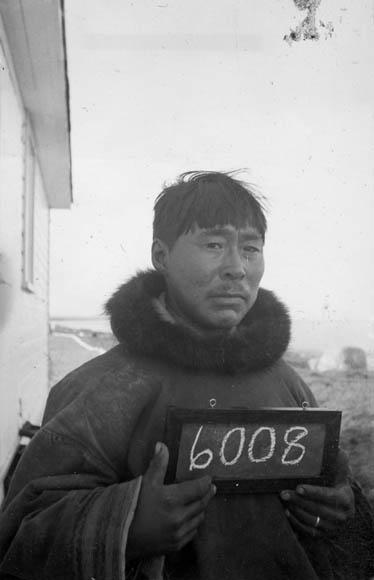 Une photographie en noir et blanc d'un homme inuit tenant un petit tableau sur lequel est écrit le numéro 6008.