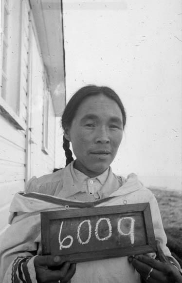 Une photographie en noir et blanc d'une femme inuite tenant un petit tableau sur lequel est écrit le numéro 6009.