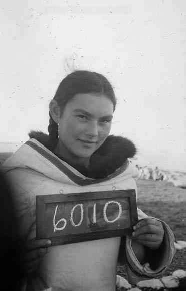 Une photographie en noir et blanc d'une femme inuite tenant un petit tableau sur lequel est écrit le numéro 6010.