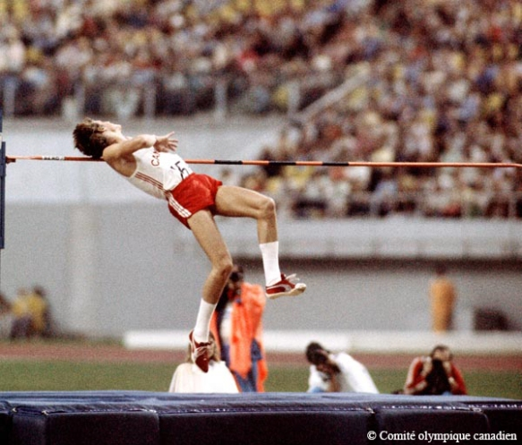 Photographie en couleur d'un homme participant à une compétition en saut en hauteur. Sur la photographie, on peut le voir dans les airs, en approche de la barre. Des photographes sont postés derrière le matelas. En arrière-plan, on voit la foule assise.