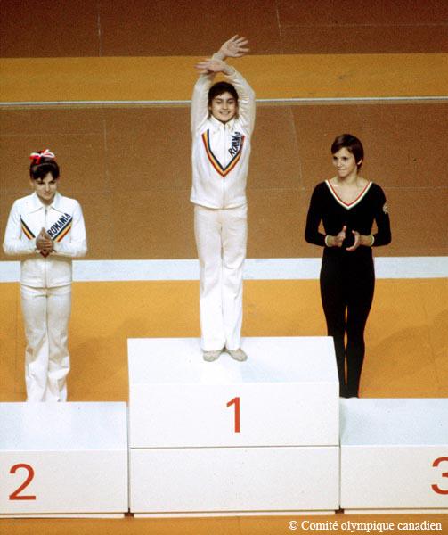 Photographie en couleur d'une jeune femme sur un podium saluant la foule. Elle porte un survêtement blanc sur lequel est écrit « Romania » (Roumanie). Il y a, derrière elle, en bas du podium, deux autres jeunes femmes.