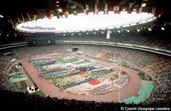 Photographie en couleur de l'intérieur du Stade olympique, à Montréal. Les athlètes représentant les pays en compétition se réunissent dans le champ intérieur du stade. Les drapeaux des pays en compétition sont suspendus aux chevrons.