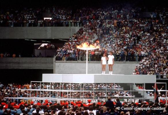 Photographie en couleur représentant deux jeunes personnes debout sur une plateforme surélevée dans un stade bondé. D'une main, chacun d'eux tient bien haut le flambeau. À côté d'eux se trouve une grande vasque cérémoniale enflammée.