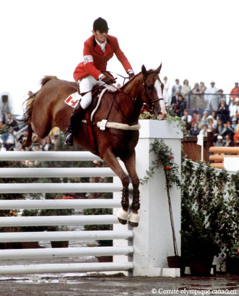 Photographie en couleur d'un homme à cheval qui franchit un obstacle durant une compétition équestre. En arrière-plan, des spectateurs sont assis.
