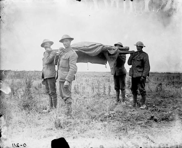 Photographie en noir et blanc de quatre soldats transportant une civière sur laquelle repose un corps recouvert d'une bâche, dans un paysage de désolation.