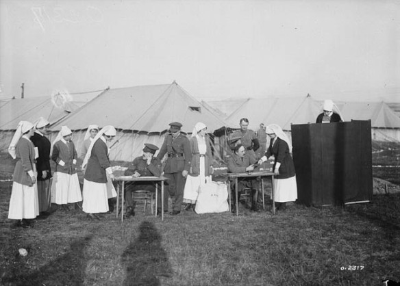Photographie en noir et blanc d'un groupe d'infirmières militaires faisant la file pour déposer leur bulletin de vote à un bureau de scrutin installé à l'extérieur d'un campement. Quatre officiers supervisent les procédures, pendant qu'une infirmière remplit son bulletin derrière un paravent. On voit des tentes à l'arrière-plan.