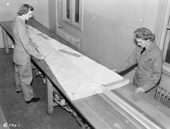 Photographie en noir et blanc de deux femmes vêtues d'une combinaison de travail, se tenant debout de chaque côté d'une longue table, sur laquelle est déposé un parachute plié.