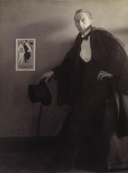 Photo noir et blanc d'un homme en tenue de soirée, debout à côté d'une affiche posée sur un mur.