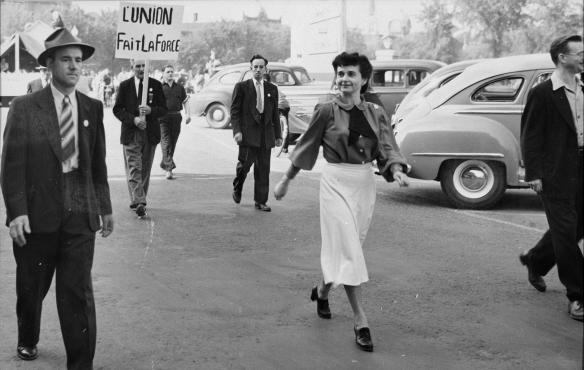 Photographie en noir et blanc d'une femme marchant dans la rue; derrière elle, un homme tient une affiche arborant le slogan « L'union fait la force ».