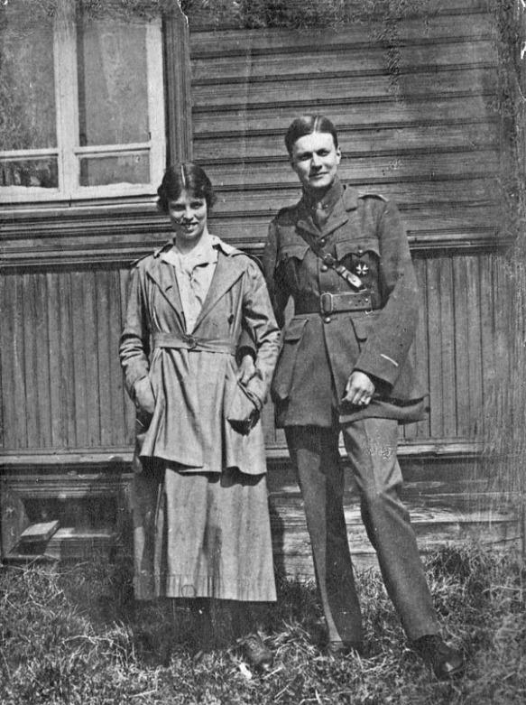 Une photographie en noir et blanc montrant un couple debout devant un bâtiment en bois. Elle porte ce qui semble être un uniforme d'infirmière et lui, un uniforme de l'armée russe.