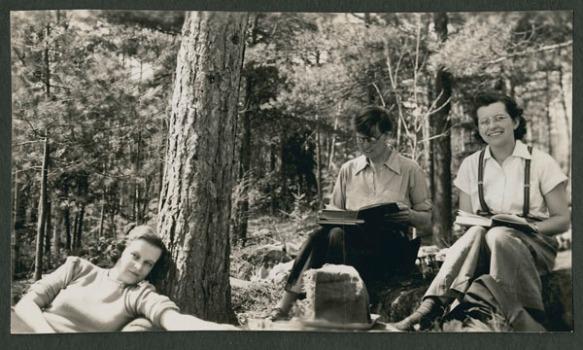 Une photographie en noir et blanc montrant trois femmes sous un arbre. La femme à droite est assise et sourit au photographe, celle qui est au milieu est également assise, mais complètement absorbée par son livre, et celle qui se trouve à gauche est allongée sur le sol et regarde le photographe.