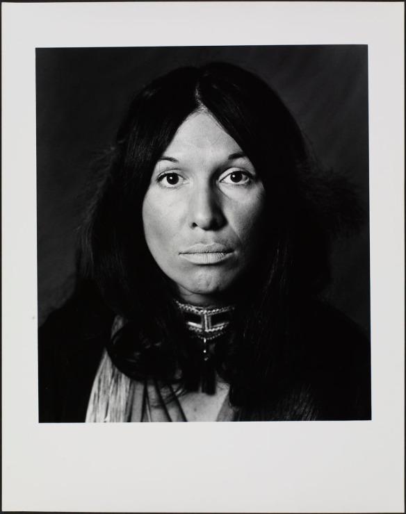 Photographie en noir et blanc d'une femme aux longs cheveux foncés qui regarde l'objectif.