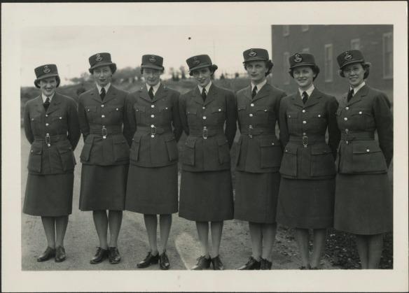 Photographie en noir et blanc de sept membres de la Division féminine de l'Aviation royale du Canada. Les femmes sont debout, dehors, les mains jointes derrière le dos et elles sourient à la caméra. Elles portent des uniformes réglementaires, dont une veste, une jupe, une casquette et des souliers.