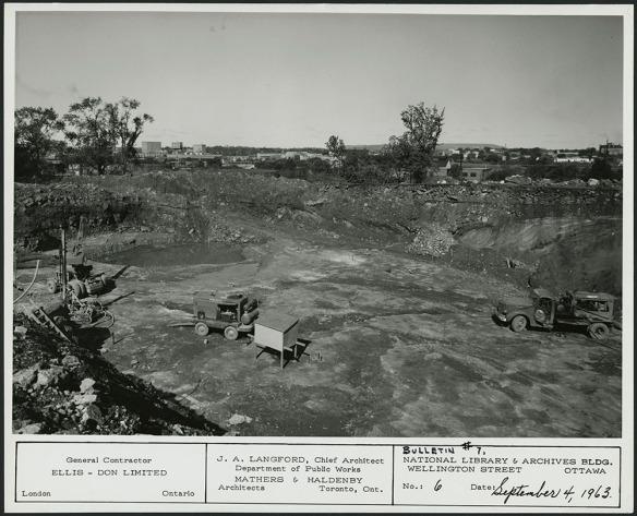 Photographie en noir et blanc d'un vaste chantier de construction avec de la machinerie lourde. On aperçoit au loin des arbres et des bâtiments.