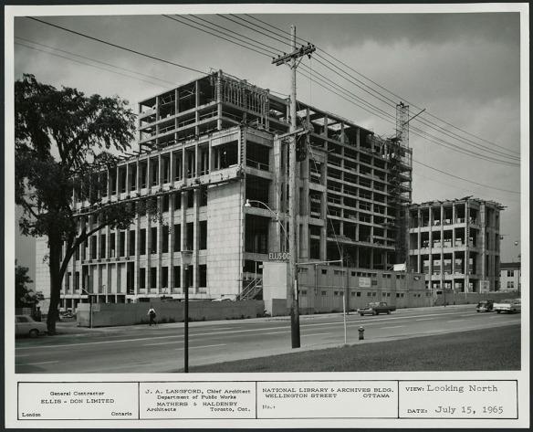 Photographie en noir et blanc de la façade d'un édifice de dix étages en construction. On voit des panneaux de construction à la hauteur du rez-de-chaussée, des automobiles (y compris une Coccinelle de Volkswagen!) et des piétons.