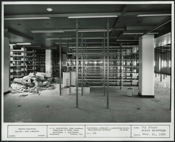 Photographie en noir et blanc d'une salle au plafond bas, avec des rangées de rayonnages superposés en cours d'aménagement.