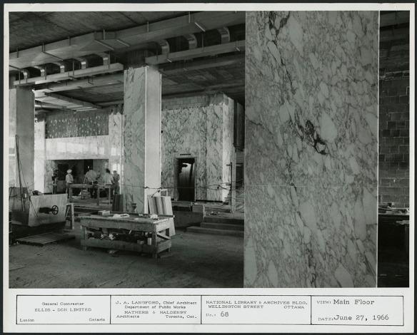 Photographie noir et blanc d'une vaste salle partiellement aménagée, aux murs recouverts de marbre de Carrare (un marbre blanc aux nervures prononcées).
