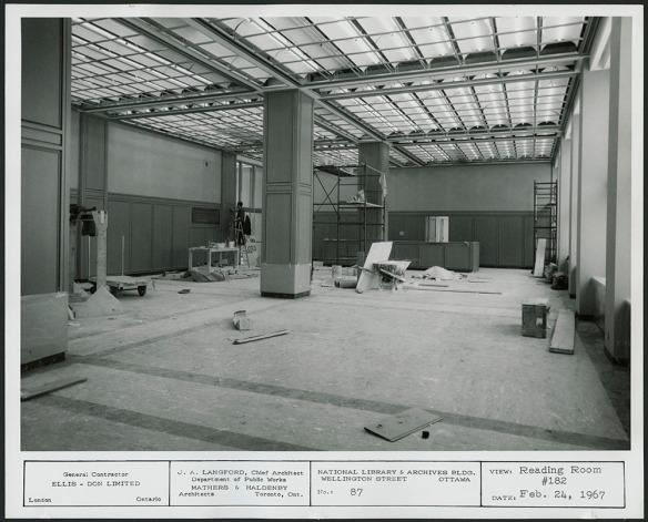 Photographie en noir et blanc d'une grande salle avec un échafaudage et des matériaux de construction.