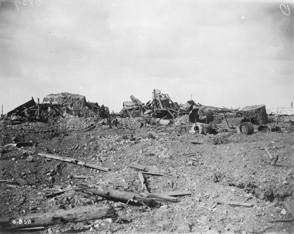 Photographie noir et blanc d'un bâtiment industriel en ruines dans un paysage dévasté.