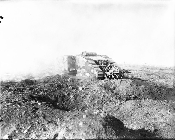 Photographie noir et blanc d'un imposant char d'assaut britannique qui avance dans un terrain criblé de cratères.