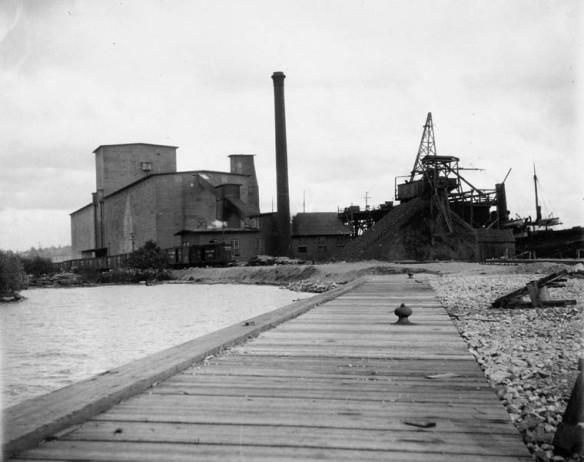 Une photographie en noir et blanc montrant un long quai en bois près d'un rivage et des silos à grains à l'arrière-plan