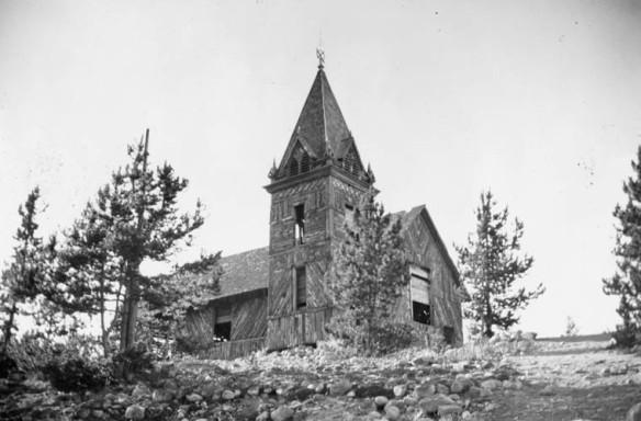 Une photographie en noir et blanc montrant une église en bois abandonnée