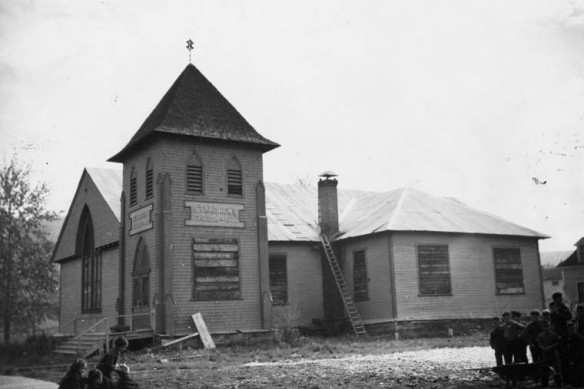 Une photographie en noir et blanc montrant une église placardée sur un terrain jonché de matériaux de construction