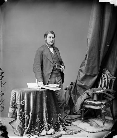 Photographie en noir et blanc d'un homme d'âge moyen portant un complet, debout à côté d'une table.
