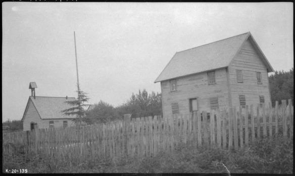 Une photographie en noir et blanc montrant deux petits bâtiments abandonnés; l'un des deux est probablement une école située derrière une clôture de bois